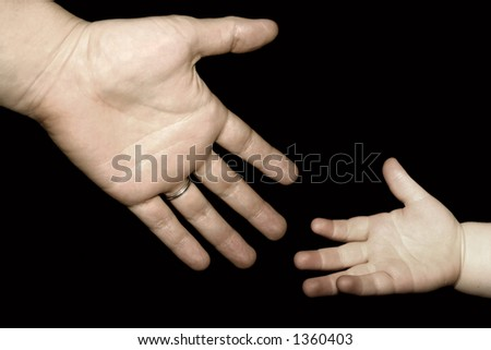 an adult reaching for a child's hand - stock photo