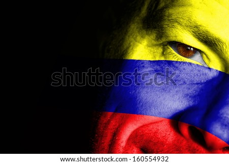 An adult sports fan with his face painted in the colors of Colombia's flag - stock photo