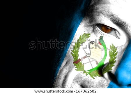 An adult sports fan with his face painted in the colors of Guatemala's flag - stock photo