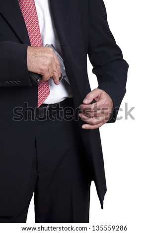 An adult wearing a suit pulling a 9mm gun out of its holster beneath the jacket. Isolated on white background. - stock photo