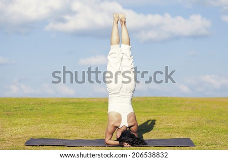An adult woman standing on her head on a black yoga mattress in the Salamba Sirsasana (aka Supported Headstand) pose, on a green lawn with cloudy blue sky in the background. - stock photo