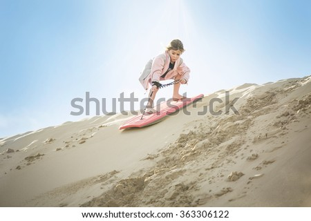 An adventuresome Little Girl boarding down the Sand Dunes  - stock photo