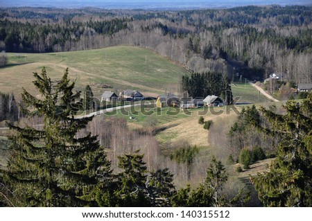 An aerial view of a village in the middle of the woods - stock photo