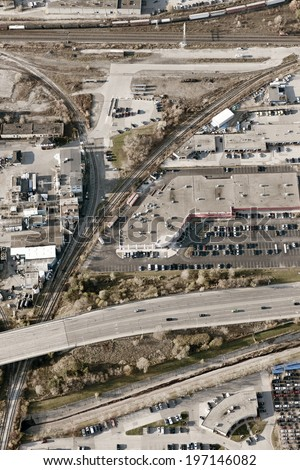 An aerial view of an industrial area filled with cars and buildings. - stock photo