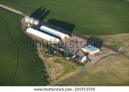 An aerial view of farm cellars for storing root vegetables with farm fields in the background - stock photo