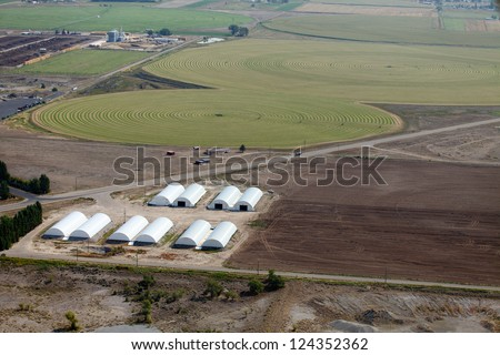 An aerial view of farm storage buildings, and irrigation circles in the field.
