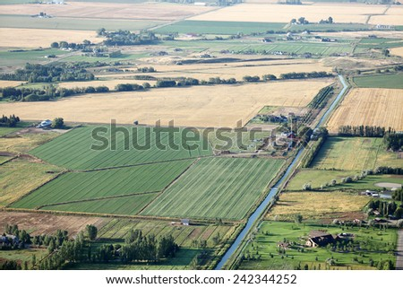 An aerial view of farmland with canals, flood irrigation, and pivot sprinklers watering the fields. - stock photo