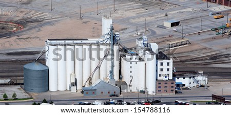 An aerial view of grain elevators for storing wheat and other cereal grains.  It is located next to a railroad siding for easy loading and unloading. - stock photo