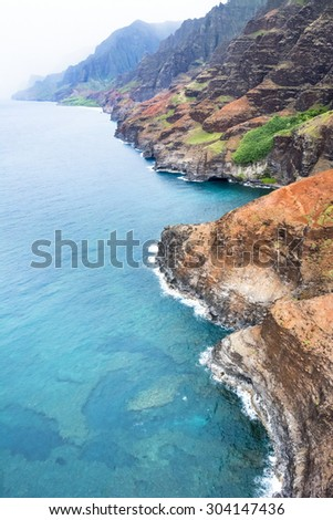 An aerial view of the Na Pali coast in Kauai Hawaii during a vibrant, sunny day shows the rich colors of the scenic coastline. - stock photo