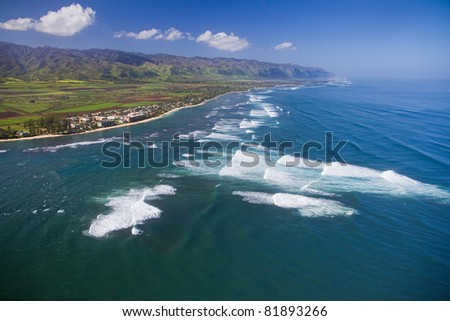 An aerial view of the surf at Waialua - North Shore of Oahu. Makuleia Beach and Kaena Point in distance. - stock photo