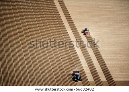 An aerial view of 2 tractors planting potatoes in the fertile farm fields of Idaho, during the spring. - stock photo