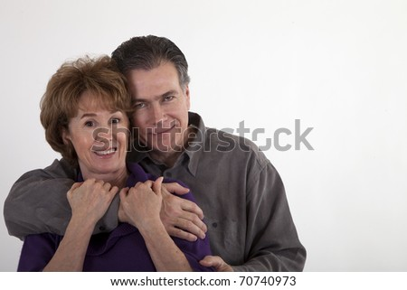 An affectionate man and a woman in their fifties or sixties smiling for the camera. - stock photo