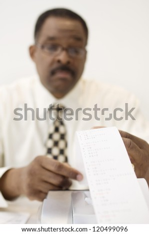 An African American accountant with expense receipt at office - stock photo