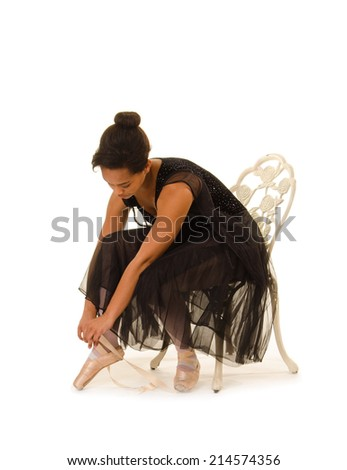 An African American Ballerina Prepares Pointe Shoes for Dance Class - stock photo