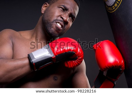 An African American boxer punches heavy bag with red boxing gloves - stock photo