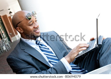 An African American business man in his early 30s using his laptop or netbook computer outdoors with copy space for your text. - stock photo