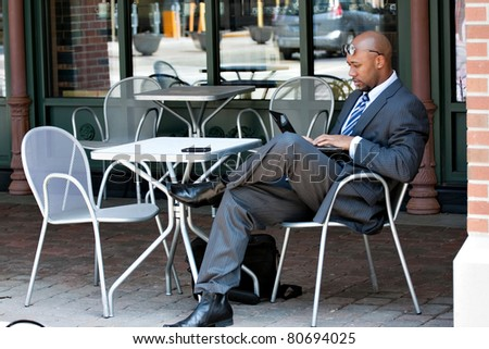 An African American business man in his early 30s using his laptop or netbook computer while seated at a cafe table outdoors. - stock photo