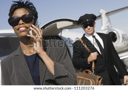 An African American business woman communicating on cell phone with driver in the background at airfield - stock photo