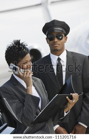 An African American business woman using cell phone while driver standing in the background at airfield