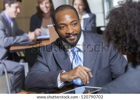 An African American businessman in a meeting with businesswoman colleague - stock photo