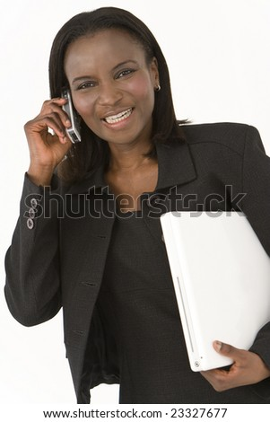 An African American businesswoman walking with a laptop under arm and chatting on her mobile phone