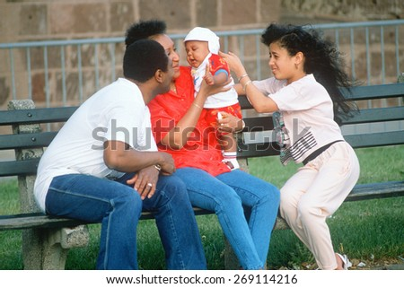 An African-American family playing with a baby on a park bench, NY City - stock photo