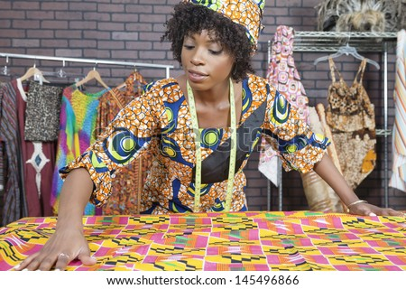 An African American female fashion designer working on a pattern cloth - stock photo