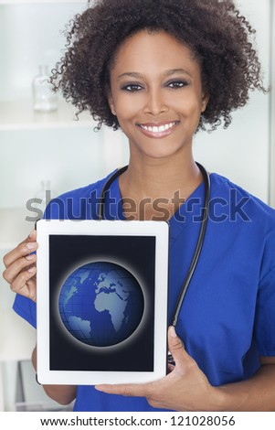 An African American female woman medical doctor with a tablet computer in hospital with a world map or globe on the screen - stock photo