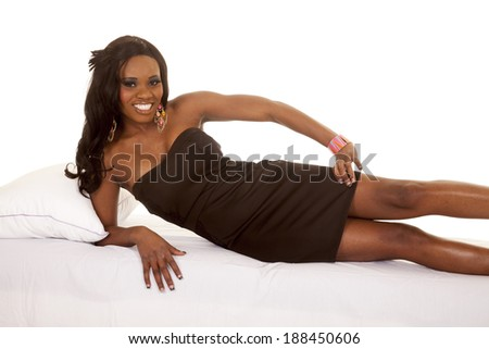 An African American laying on her bed in her black dress. - stock photo