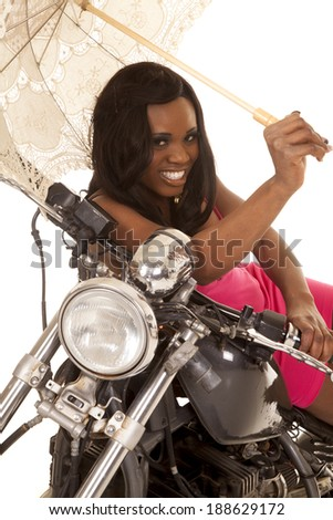an African American laying on her motorcycle in her pink dress, and umbrella. - stock photo