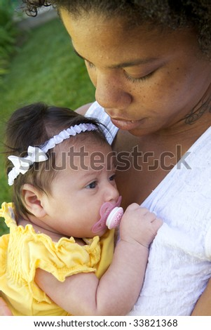 An African American Mother holder her child with a pacifier - stock photo