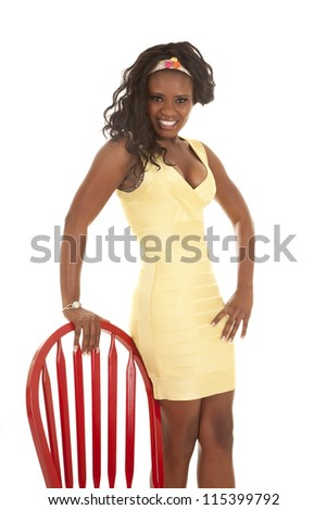 An African American standing next to a red chair in her yellow dress with a smile on her face. - stock photo