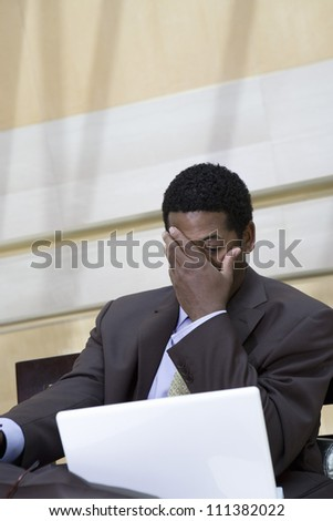 An African American tensed businessman looking at laptop