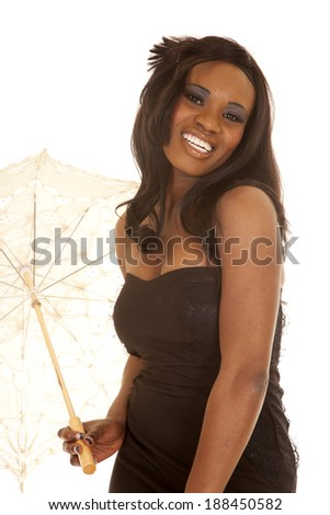 an African American with a smile on her face holding on to an umbrella. - stock photo