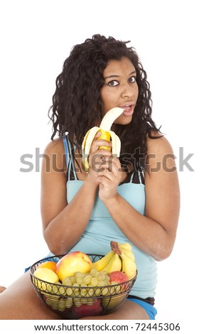 An African American woman is biting a banana.