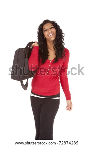An African American woman is holding a bag over her shoulder. - stock photo