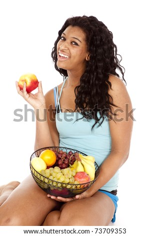 An African American woman is holding a big basket of fruit. - stock photo