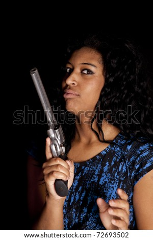 An African American woman is holding a big gun. - stock photo