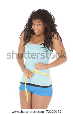 An African American woman is measuring her waist.