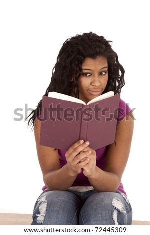 An African American woman is reading a book. - stock photo