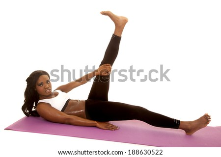 An African American woman laying on her mat with her leg up stretching.