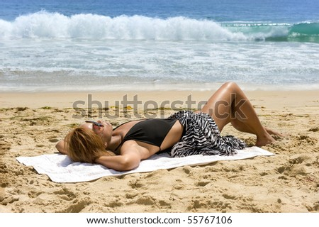 An African American woman relaxes at the beach while sunbathing. - stock photo