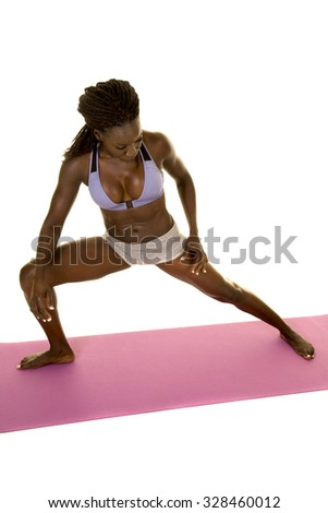 An African American woman stretching out her body, on a fitness mat. - stock photo