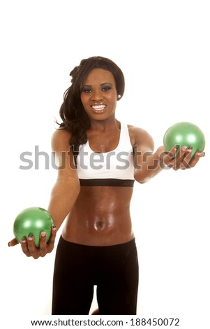 an African American woman working out with green weighted balls.