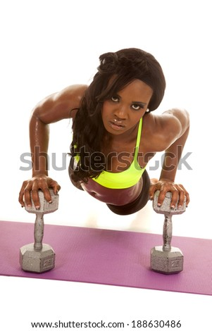 an African American woman working out with weights doing a push up. - stock photo