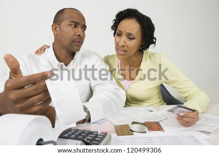 An African American worried couple with expense receipt and credit cards at home - stock photo