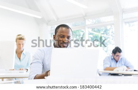 An African Businessman Working On Laptop in Office - stock photo