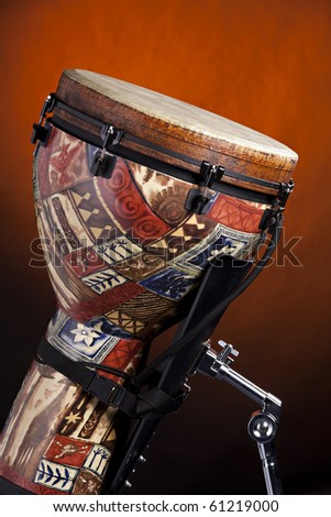 An African or Latin djembe drum isolated against a spotlight gold background. - stock photo