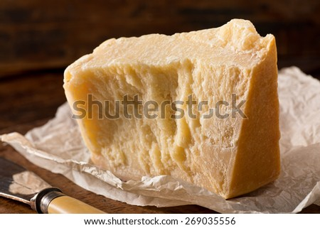 An aged authentic parmigiano reggiano parmesan cheese with wrapper and cheese knife. - stock photo