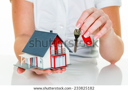 an agent for property with a house and a key. successful leasing and home sales by real estate agents. - stock photo
